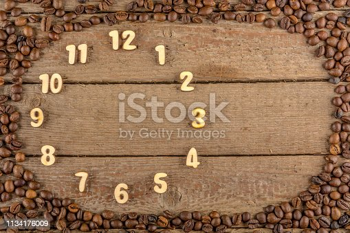 istock Decorative clock with wooden numbers on a wooden background and a frame of coffee beans 1134176009