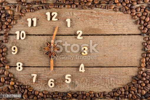 Decorative clock with wooden numerals and arrows made of cinnamon sticks, showing 6 o'clock, on a wooden background and a frame of coffee beans. Kitchen, advertising, banner, Copy space,  Flat Lay.