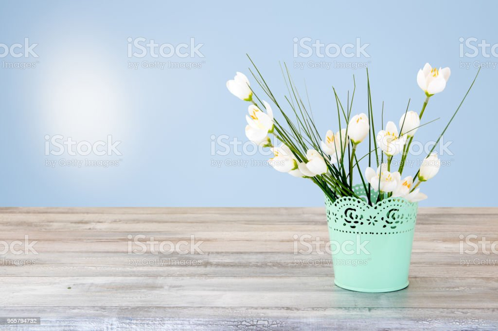 Composição decorativa de Bouquet de flores brancas na rústica mesa de madeira brilhante. Cartão do conceito. O fundo natural brilhante com o sol está brilhando. O ramo de flores brancas é no vaso decorativo verde.  Espaço vazio para seu projeto. Conceito de cartão para as mães - foto de acervo
