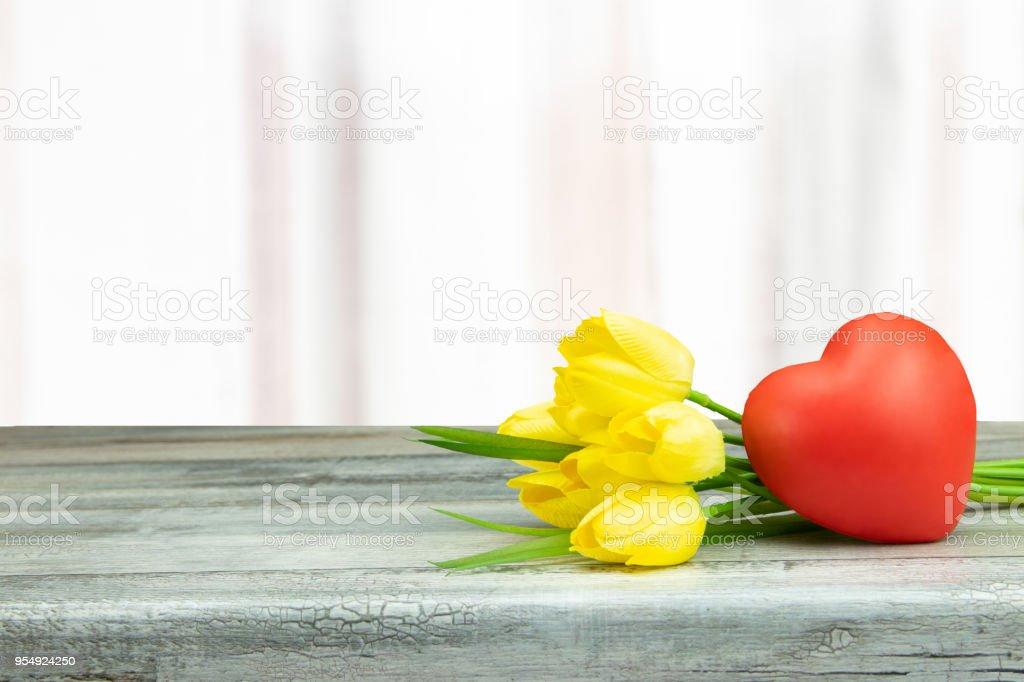 Composição decorativa de tulipas amarelas e um coração vermelho na rústica mesa de madeira brilhante. Cartão do conceito. Dia das mães. - foto de acervo