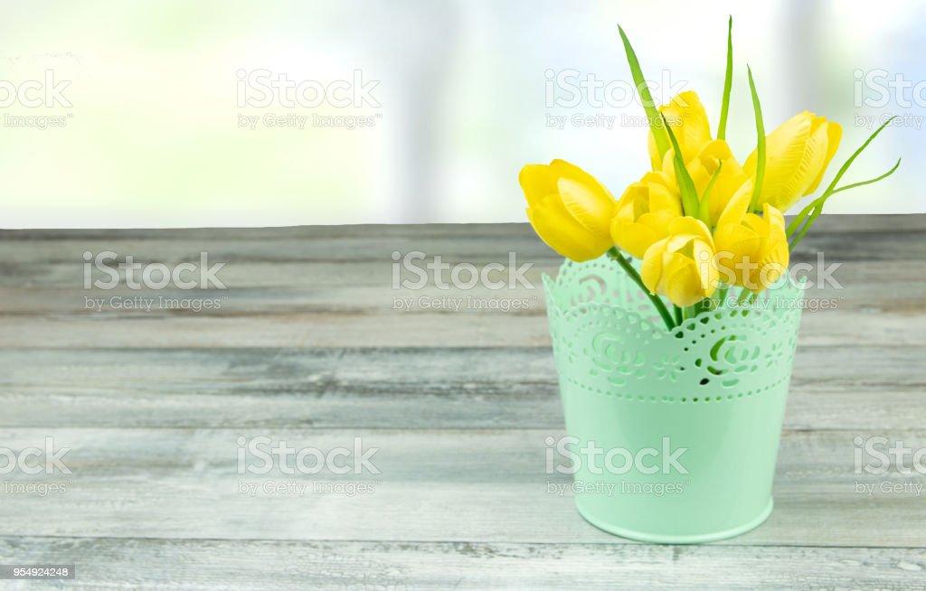 Composição decorativa de tulipas amarelas na rústica mesa de madeira brilhante. Cartão do conceito. - foto de acervo