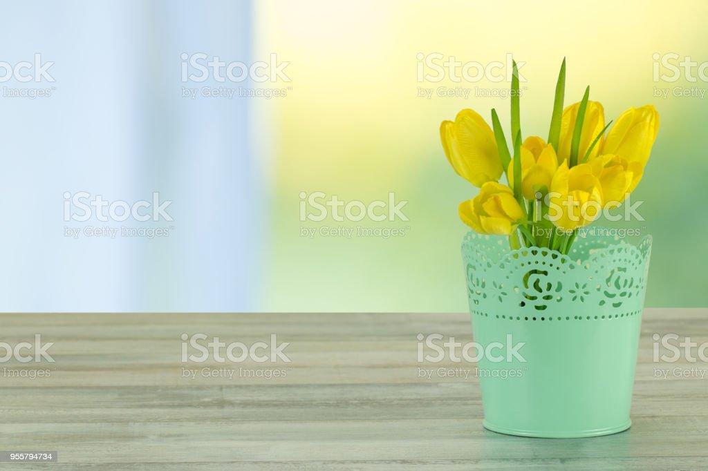 Composição decorativa de tulipas amarelas na rústica mesa de madeira brilhante. O fundo brilhante brilhante é símbolo da primavera. O bando de tulipas amarelas está no vaso decorativo verde. Espaço vazio para seu projeto. Conceito de cartão para o dia das mães, aniversário, Anversa - foto de acervo