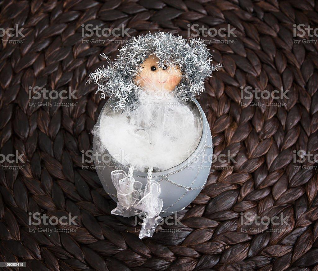 Decorative doll sitting in the ceramic bowl stock photo