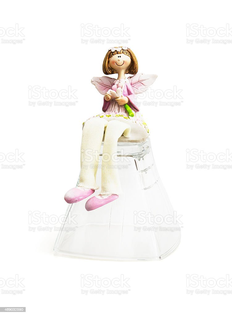 Decorative doll sitting on the glass cup stock photo