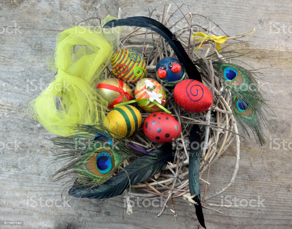 Decorative Easter eggs in nest with feathers stock photo