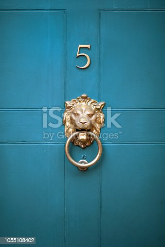 Decorative, elegant brass lions head door knocker on an old Georgian style teal coloured panelled front door