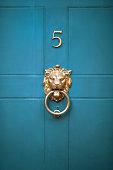 istock Decorative, elegant brass lions head door knocker on an old Georgian style teal coloured panelled front door 1055108402