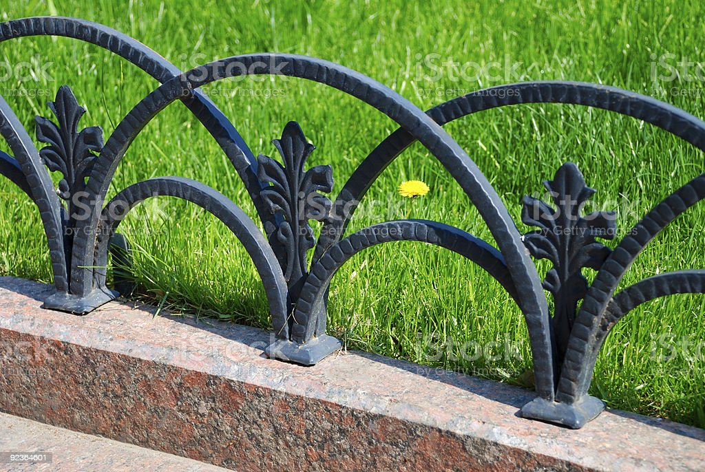 Decorative fencing near sidewalk in park royalty-free stock photo