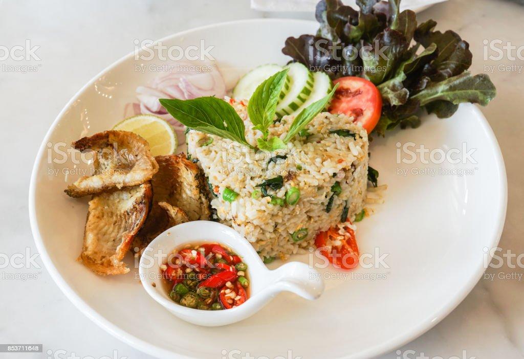 Decoratieve gebakken rijst met krokante vis op witte plaat in