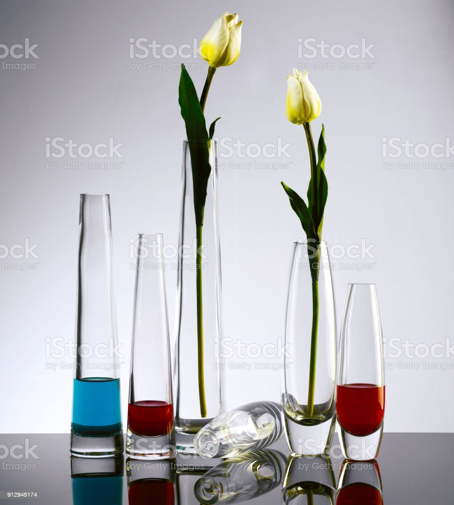 Decorative glass vase with artificial flowers on black background.