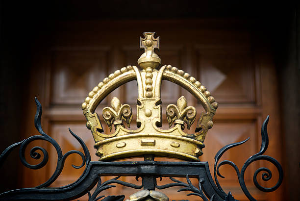 Decorative Gold Crown on Wrought Iron Gate A decorative, gilded crown on a wrought iron fence outside London's National Portrait Gallery with a wood panel door in the background. royalty stock pictures, royalty-free photos & images