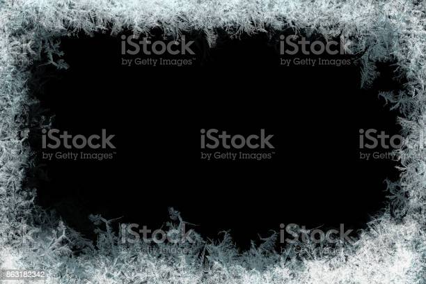 Photo of Decorative ice crystals frame on black matte background