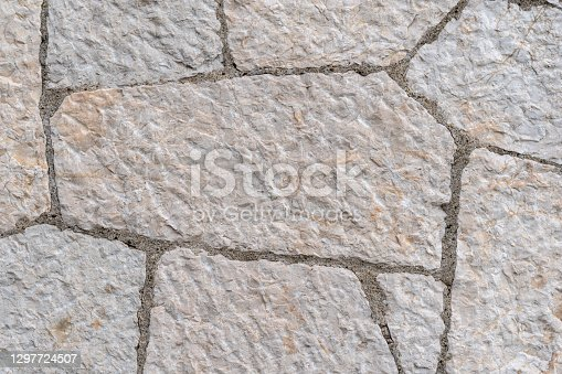 Decorative limestone on facade of the building as a background or backdrop. stone wall texture background. Brickwork or stonework flooring interior rock pattern clean grid of uneven bricks stack.