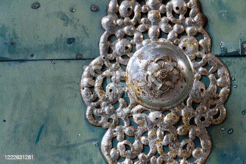Decorative metallic handle on ironwork doors fittings, vintage light blue gate, azure color