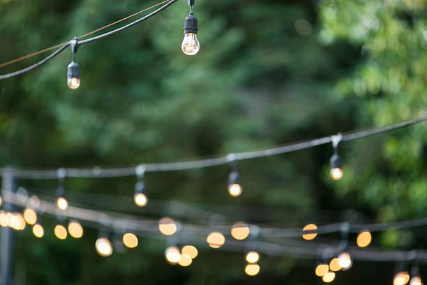 dekorative outdoor-party lights auf den garten - grüne hochzeit themen stock-fotos und bilder