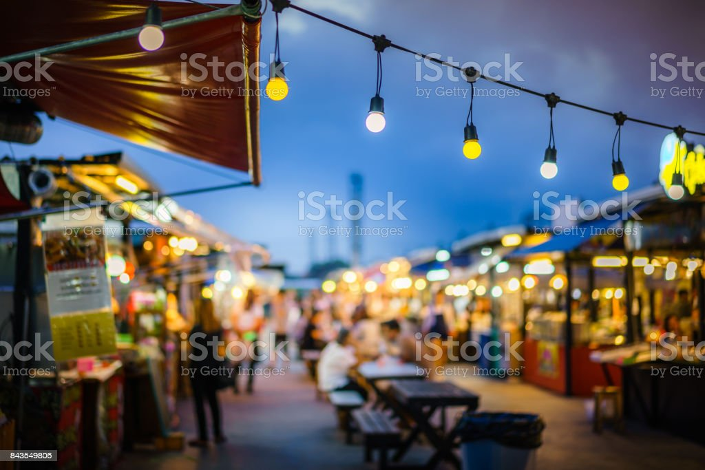 Decorative outdoor string lights hanging on electricity post in the garden at night time with blur people. Christmas,festival, holiday and wedding concepts. stock photo