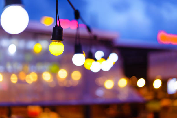 Decorative outdoor string lights hanging on electricity post in the garden at night time with blur people. Christmas,festival, holiday and wedding concepts. Decorative outdoor string lights hanging on electricity post in the garden at night time with blur people. Christmas,festival, holiday and wedding concepts. night market stock pictures, royalty-free photos & images