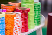 istock Decorative paper tapes in detail, colorful tapes lay in reels piles. Ribbons in the store a large selection 1087642460