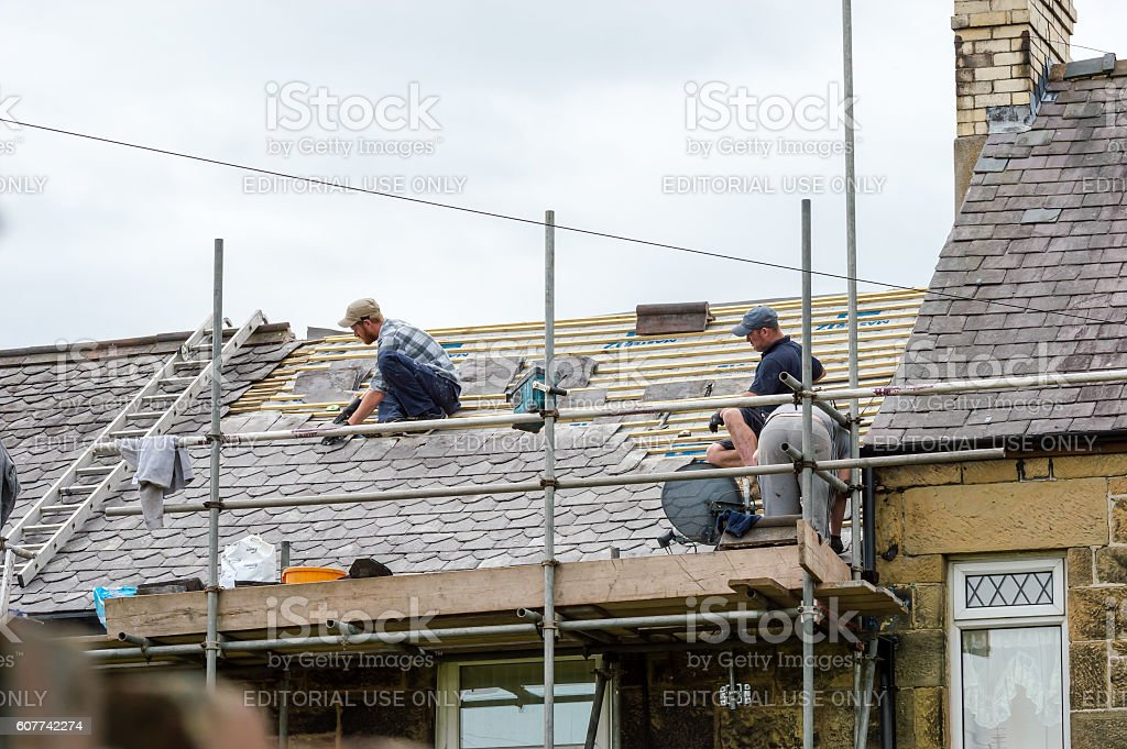 Decorative slate roof restoration in Wales. Wrexham, Wales, United Kingdom - August 10, 2016: Restoration of decorative slate roof on a residential terraced house in North Wales. With three workmen. Adult Stock Photo