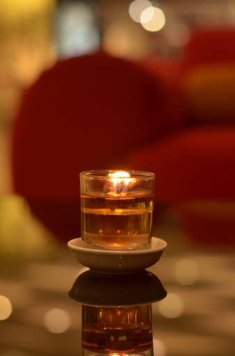 Decorative Spa Candle or tea light on glass table with blurred background