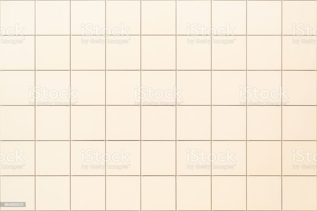 Decorative square beige tile on the facade of the building as a background or backdrop stock photo