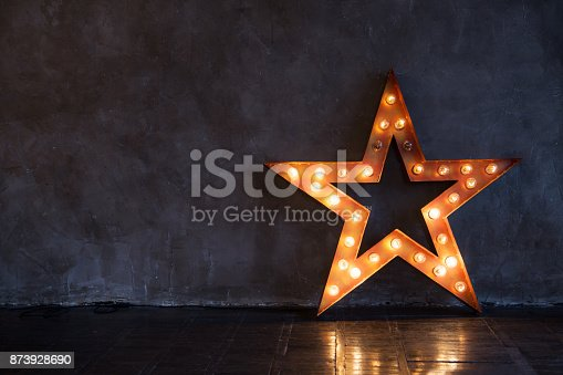 istock Decorative star with lamps on a background of wall. Modern grungy interior 873928690