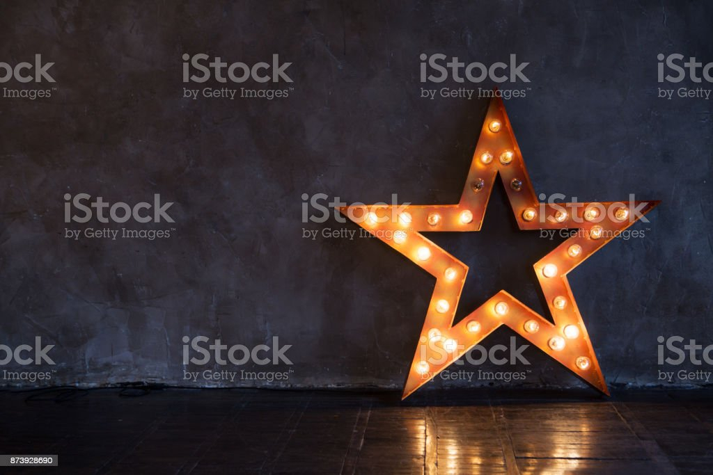 Decorative star with lamps on a background of wall. Modern grungy interior stock photo