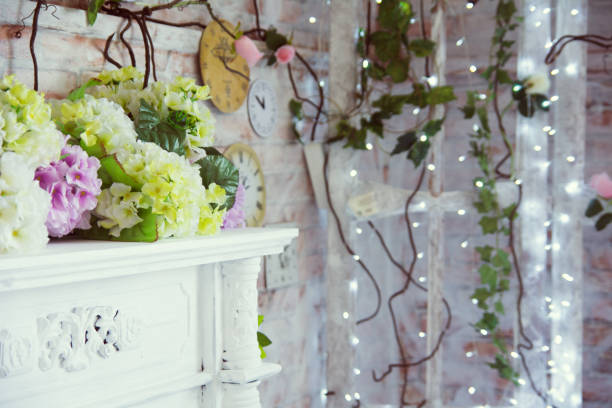 Decorative table with artificial flowers and a background of burning garlands stock photo