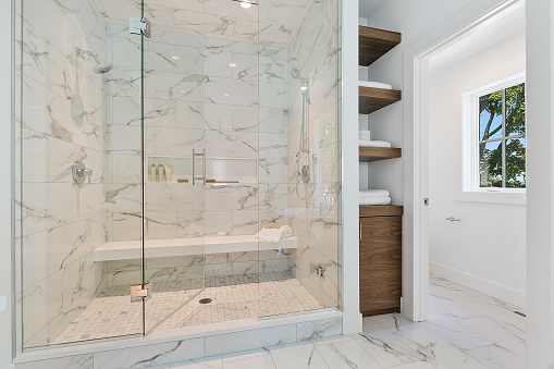Long bench in shower and full glass entry to shower