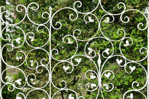 barrière blanche décorative avec des boucles sur le fond d'un buisson vert. - motif ornemental photos et images de collection