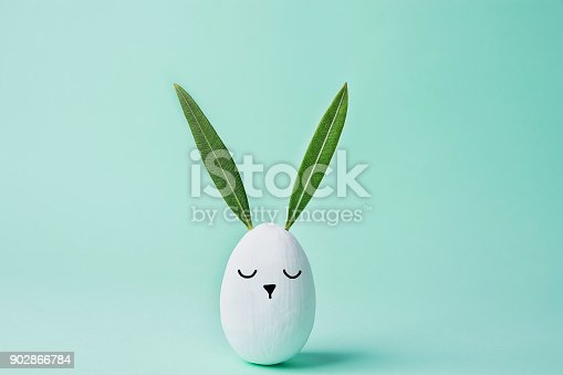 istock Decorative White Painted Easter Egg Bunny with Drawn Cute Kawaii Face. Green Leaves as Ears. Pastel Turquoise Background. Spring Holiday Crafts Kids Concept. Greeting Card Poster Banner. Copy Space 902866784