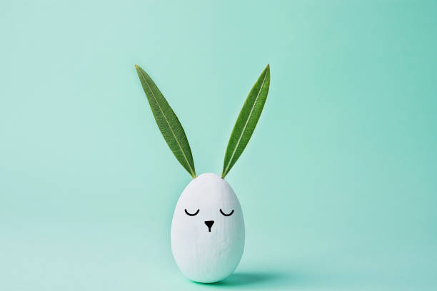 decorative white painted easter egg bunny with drawn cute kawaii face. green leaves as ears. pastel turquoise background. spring holiday crafts kids concept. greeting card poster banner. copy space - easter foto e immagini stock