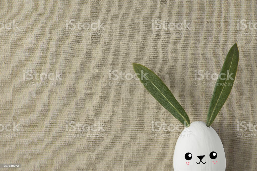 Decorative White Painted Easter Egg Bunny with Drawn Cute Kawaii Smiling Face. Green Leaves Ears. Beige Linen Fabric Background. Holiday Crafts Kids Concept. Greeting Card Poster Banner. Copy Space stock photo
