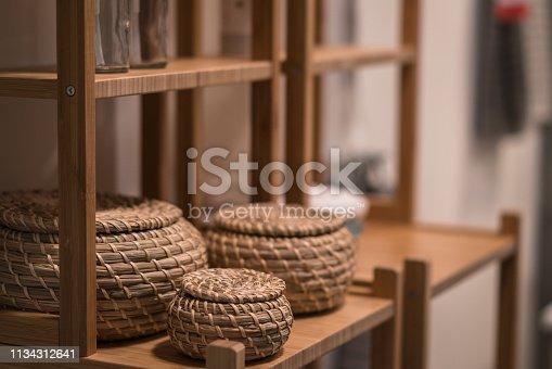 Decorative wicker baskets in bathroom shelf