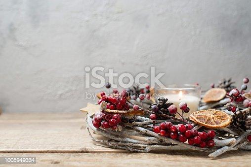 istock Decorative winter wreath with red berries, cones and slices of orange 1005949334