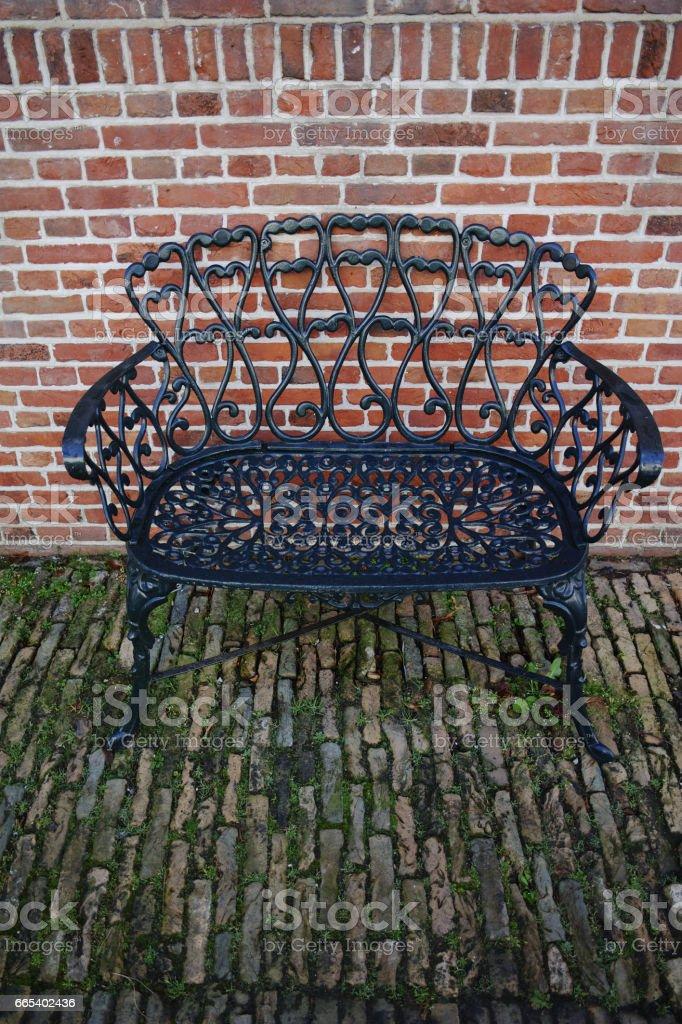 Banco de hierro forjado decorativo en el jardín - foto de stock