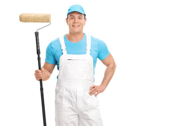 decorator holding a paint roller - painter stock photos and pictures