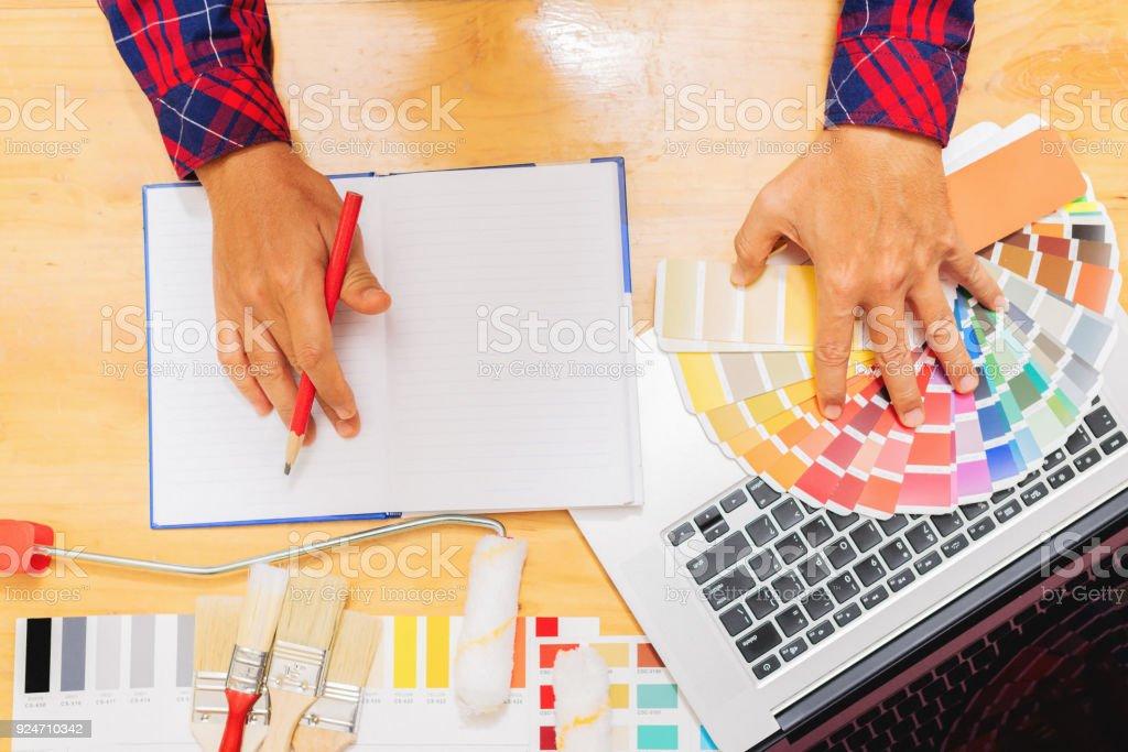 Dekorateur mit Laptop mit House-Projekt. – Foto