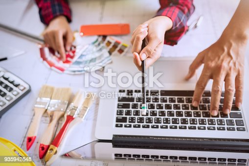 istock Decorator using laptop with house project. 935942648