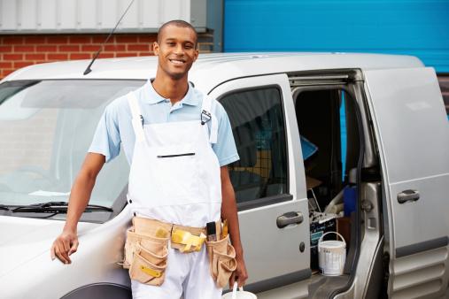 Decorator Wearing Overalls Standing Next To Van Smiling At Camera