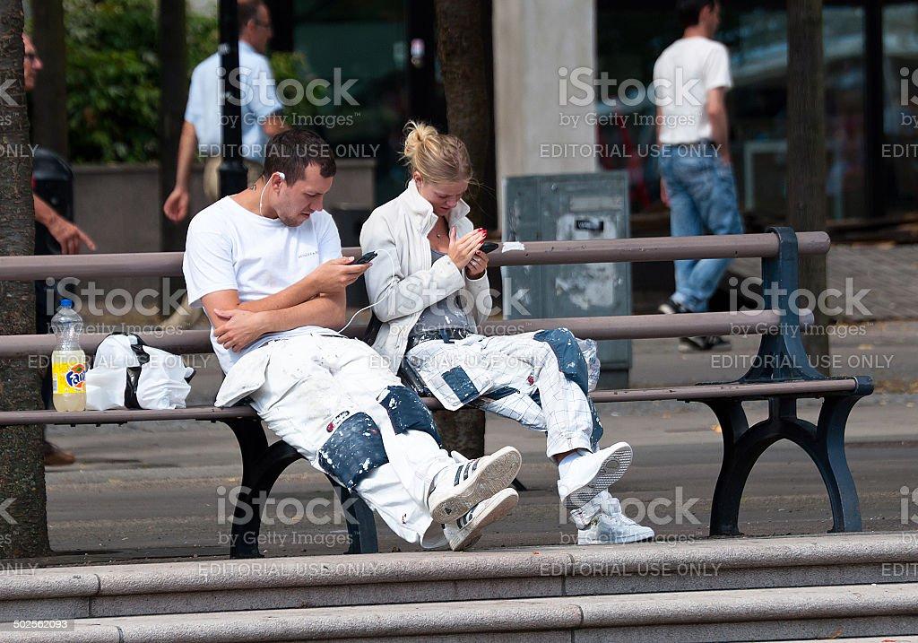 Decorators check their phones stock photo