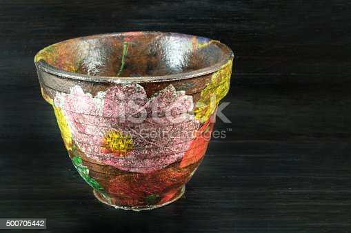 Decoupage decorated flower pot  against black wooden background