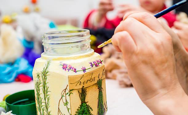 decoupage decoupage bottle. Professional painter paints a souvenir artistical stock pictures, royalty-free photos & images