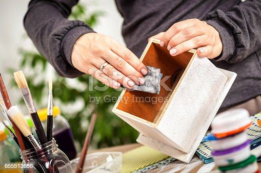 Woman hands taking sand paper on wooden box