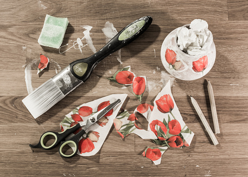Decoupage accessories laid out on a table. Paintbrush, scissors, pencils, sponge and paper in messy arrangement, Overhead view.
