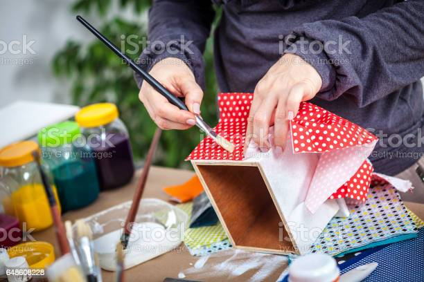 Woman hands decoupaging and painting wooden box