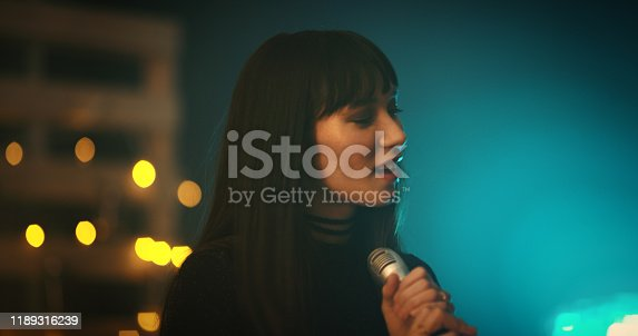 Shot of a young woman singing on stage
