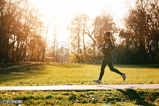 Full length of black sportswoman jogging in nature. Copy space.
