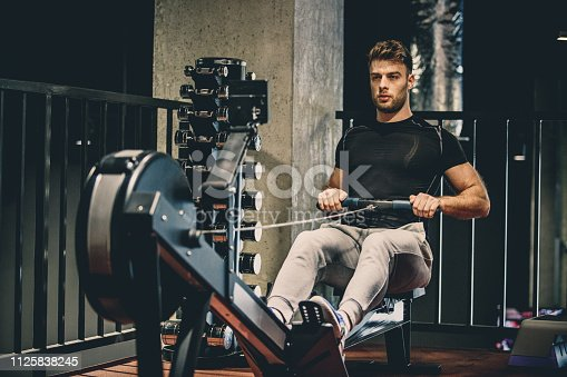 Caucasian young man is using rowing machine for cardio training in the gym.