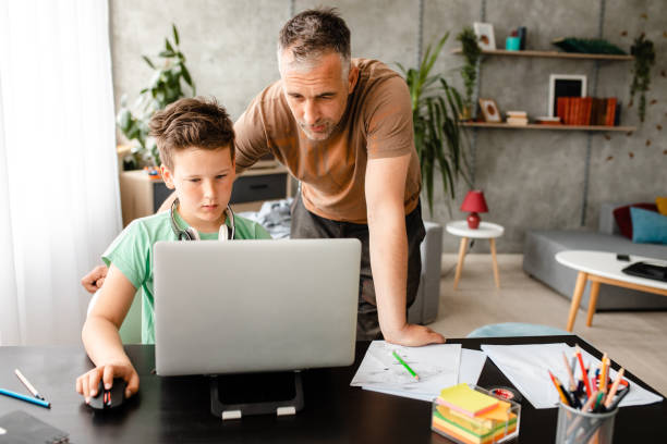 Dedicated father helping his son to do the research on internet for a homework stock photo